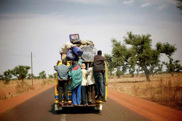 Malians hang on the back of a packed minibus as they drive to Marakala, central Mali, some 240kms (140 miles) from Bamako Tuesday, Jan. 22, 2013.  French troops in armored personnel carriers rolled through the streets of Diabaly on Monday, winning praise from residents of this besieged town after Malian forces retook control of it with French help a week after radical Islamists invaded. The Islamists also have deserted the town of Douentza, which they had held since September, according to a local official who said French and Malian forces arrived there on Monday as well. (AP Photo/Jerome Delay) Photo: Jerome Delay