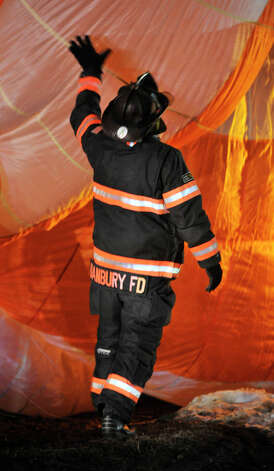 A Danbury firefighter attempts to manage a parachute that was used in an airplane that crashed near the corner of South Street and Wixted Avenue in Danbury on Tuesday, Jan. 22, 2013. Photo: Jason Rearick / The News-Times