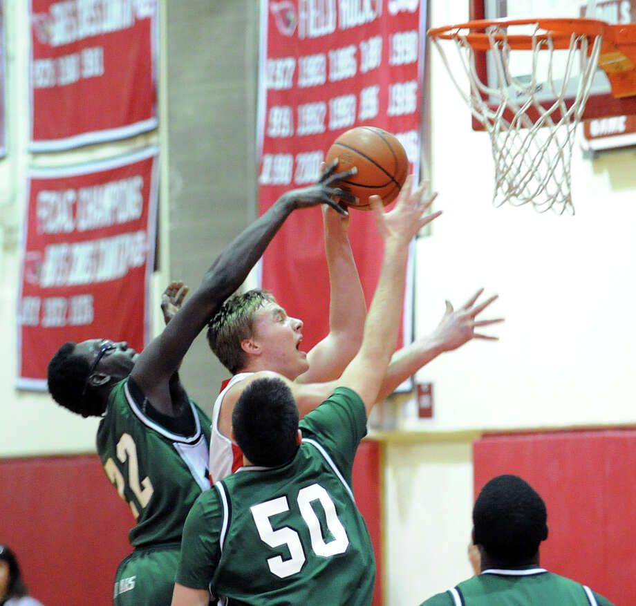 At left, Roy Kane of Norwalk blocks the shot of Alex Wolf of Greenwich as Sean Butler # 50, also of Norwalk, looks on during the boys high school basketball game between Greenwich High School and Norwalk High School at Greenwich, Tuesday night, Jan. 22, 2013. Photo: Bob Luckey / Greenwich Time