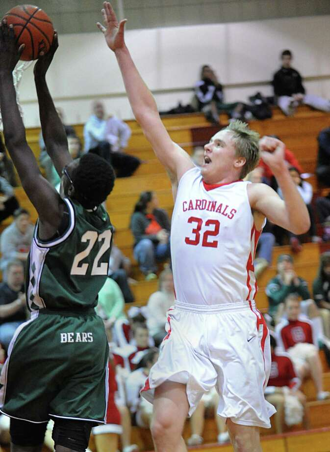 At left, Roy Kane # 22 of Norwalk gets his shot blocked from behind by Alex Wolf # 32 of Greenwich during the boys high school basketball game between Greenwich High School and Norwalk High School at Greenwich, Tuesday night, Jan. 22, 2013. Photo: Bob Luckey / Greenwich Time