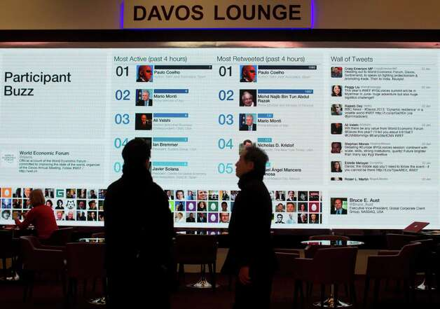 People gather at the 'Davos lounge'  inside the Congress Center and follow the latest tweets of participants on the eve of the opening of the 43rd Annual Meeting of the World Economic Forum, WEF, in Davos, Switzerland, Tuesday, Jan. 22, 2013. As corporate leaders gather for the World Economic Forum in Davos amid a slow and shaky recovery, a new study looks at business leaders' moods and what they hope to do this year.  (AP Photo/Anja Niedringhaus) Photo: Anja Niedringhaus