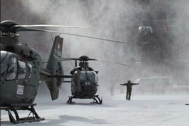 A Swiss army airman guides a EC 635 helicopter for landing at an army base in Davos where the annual meeting of the World Economic Forum will start on the upcoming Wednesday, Tuesday, Jan.  22, 2013. 3500 soldiers are mobilized to secure the annual meeting of the World Economic Forum in Davos. (AP Photo/Michel Euler) Photo: Michel Euler