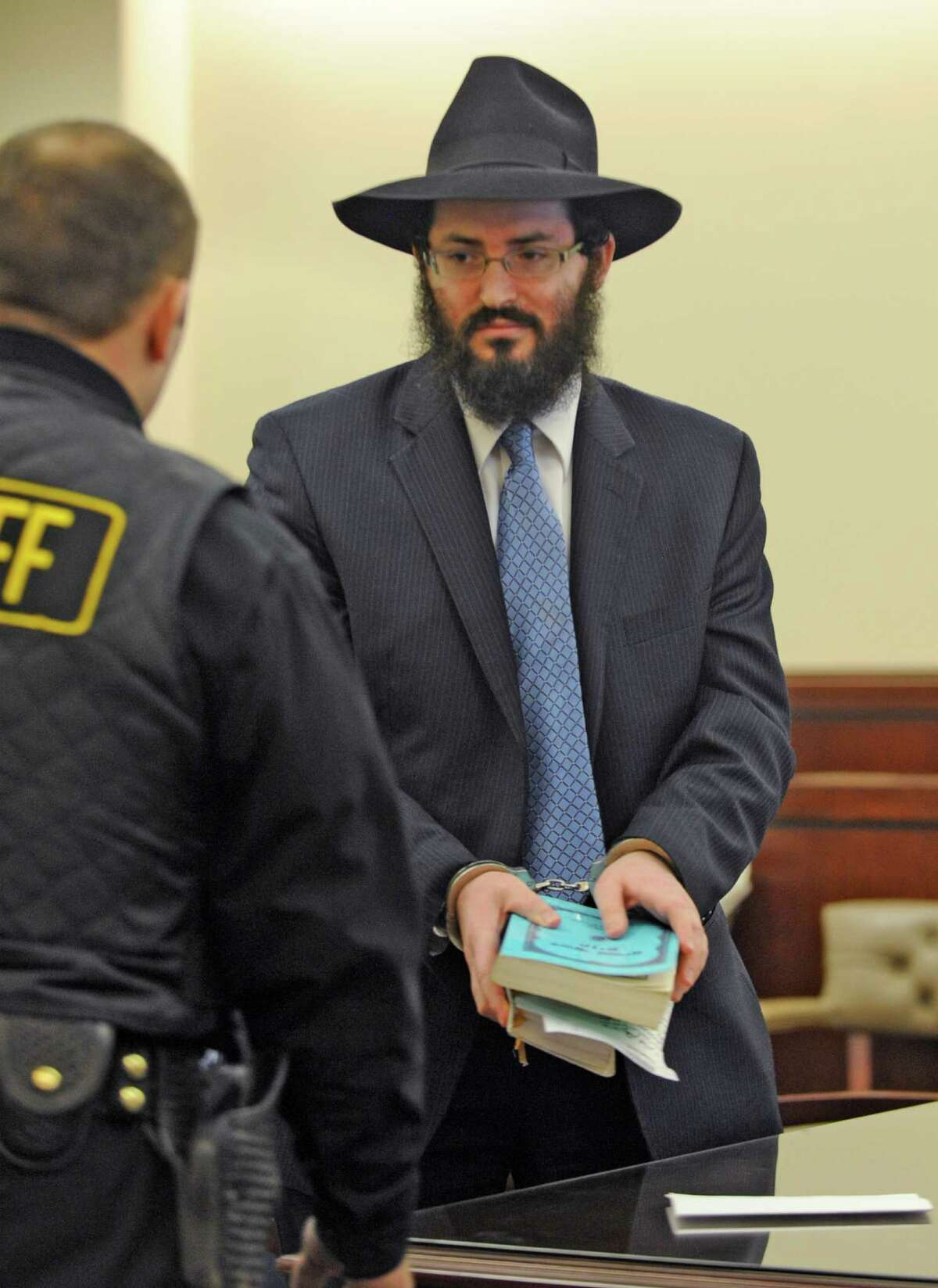 Yaakov Weiss holds his prayer books and wears handcuffs at the Albany County Judicial Center in Albany, New York, on March 8, 2010, after being sentenced to Albany County Jail for child endangerment (Skip Dickstein/Times Union archive)