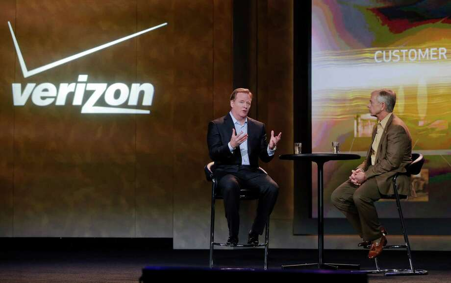 FILE - In this Jan. 8, 2013, file photo, NFL football commissioner Roger Goodell, left, and Verizon CEO Lowell McAdam talk about Verizon mobile products that allow NFL fans to watch games and interact with each other at the Consumer Electronics Show, in Las Vegas. The parent of the country's biggest wireless carrier lost $4.23 billion, or $1.48 per share, for the period ended Dec. 31. That compares with a loss of $2.02 billion or 71 cents per share, a year ago. (AP Photo/Julie Jacobson) Photo: Julie Jacobson