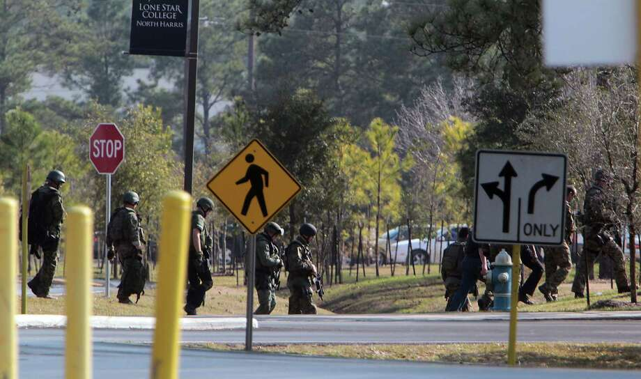 SWAT officers search the Lone Star College parking lots and buildings after a shooting which left several people injured Tuesday, Jan. 22, 2013, in Houston. Photo: James Nielsen, Chronicle / © Houston Chronicle 2013