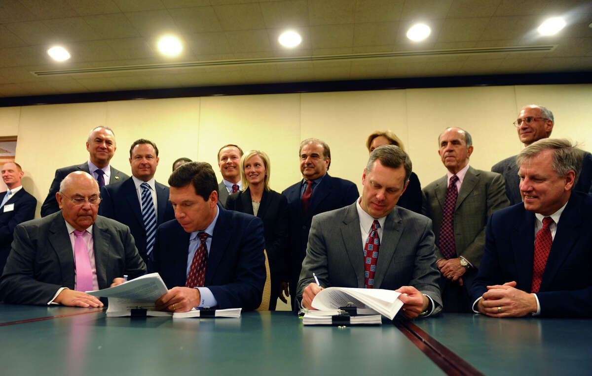 A signing ceremony to announce Norwalk Community Hospital's affiliation with Western Connecticut Health Network was held at Dolce Norwalk Conference Center in Norwalk, Conn. on Tuesday January 22, 2013. Trustee Victor Liss, left, witnesses Western CT Health Network President and CEO John Murphy sign paperwork and trustee James Kennedy, right, witnesses as Norwalk Hospital President and CEO Dan Debarba signs as well.