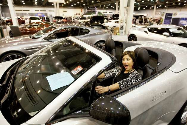 April Sanchez of KPRC Channel 2 clowns around in a Aston Martin Vintage S sports car as her friends take her picture during the Houston Autoshow 30th Preview presented by the Houston Chronicle, Tuesday, Jan. 22, in Reliant Center in Houston. The Auto show begins today and finishes on January 27th. The show offers rides and drives allowing drivers a chance to evaluate new vehicles and a kids fun zone amongst other things. Photo: Nick De La Torre, Houston Chronicle / © 2013  Houston Chronicle