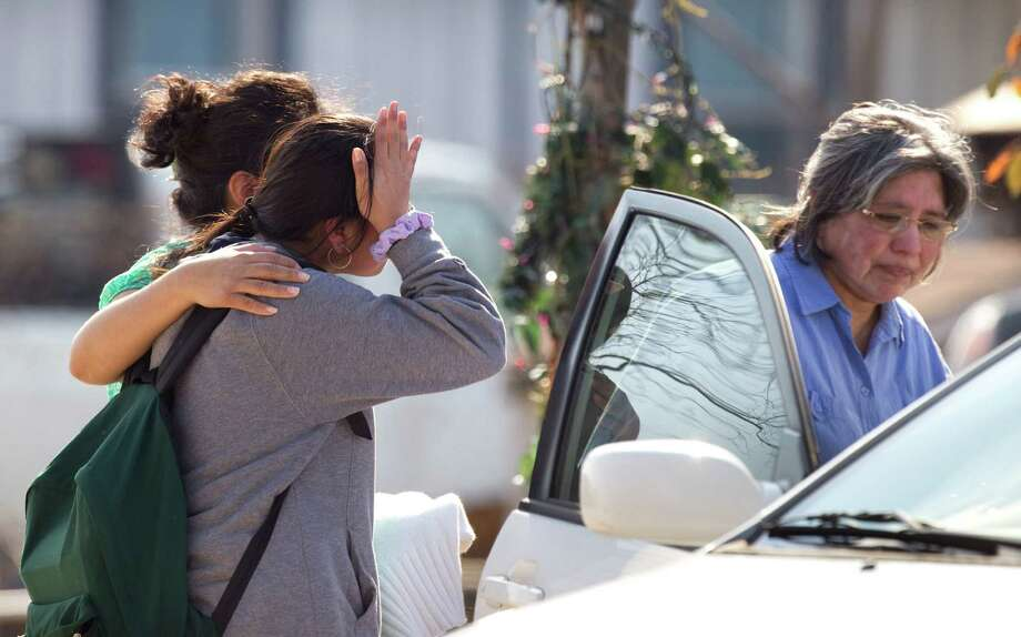 Ana Leal, left, embraces Lone Star College student Sabrina Cuellar after she was evacuated and picked up by her mother, Maria Cuellar, right, from the campus following a shooting at the north Harris County school Tuesday, Jan. 22, 2013, in Houston. Photo: Brett Coomer, Houston Chronicle / © 2013 Houston Chronicle