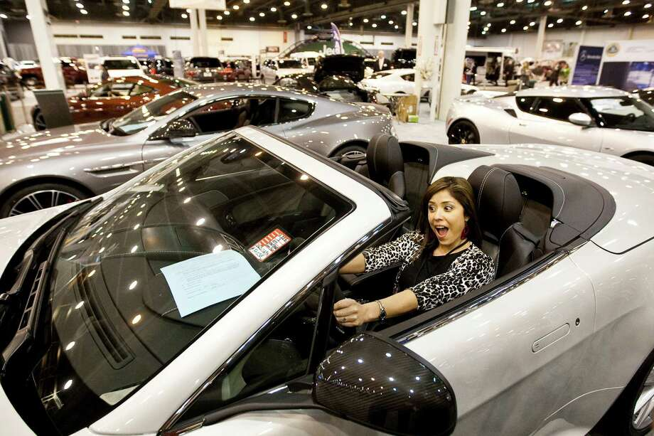 April Sanchez of KPRC Channel 2 clowns around in an Aston Martin Vintage S sports car on Tuesday at the 30th Anniversary Preview Night presented by the Chronicle at Reliant Center on Tuesday. The Auto Show begins on Wednesday and finishes on Jan. 27. The show allows drivers a chance to evaluate new vehicles. Photo: Nick De La Torre, Houston Chronicle / © 2013  Houston Chronicle