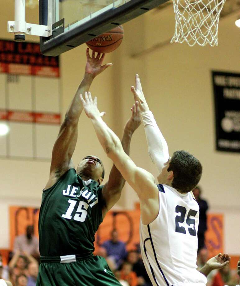 Strake Jesuit's Reveal Chekwujekwu (15) goes hard to the basket over Seven Lake's  Ryan McClurg (25) during a District 19-5A basketball game between Strake Jesuit and Seven Lakes, Tuesday, Jan.22, 2013. Photo: Bob Levey, Houston Chronicle / ©2013 Bob Levey