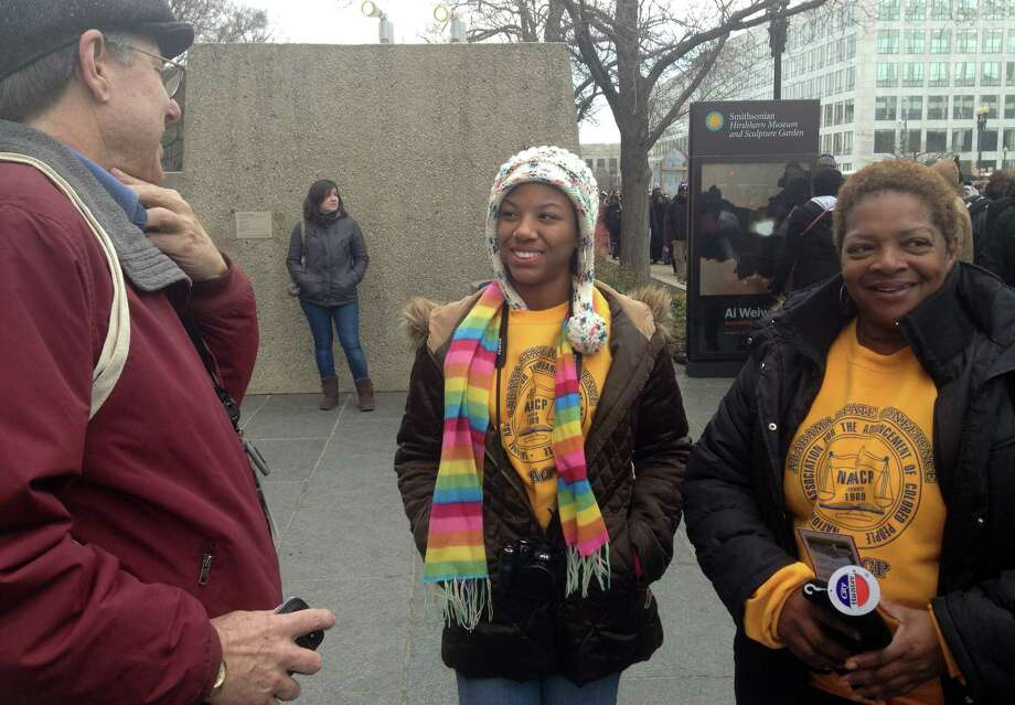 Curator William Pretzer talks with Ollie Parham, 55, of Huntsville, Ala., right, and her niece who rode on a bus all night to get to the inauguration with a group from the state NAACP conference Monday, Jan. 21, 2013, at the inauguration in Washington. Pretzer, a curator from the Smithsonian National Museum of African American History and Culture, was asking for objects to be donated for future exhibitions. The Smithsonian's National Museum of African American History and Culture will open its doors during President Barack Obama's second term with a large display about the first black president. (AP Photo/Brett Zongker) Photo: Brett Zongker