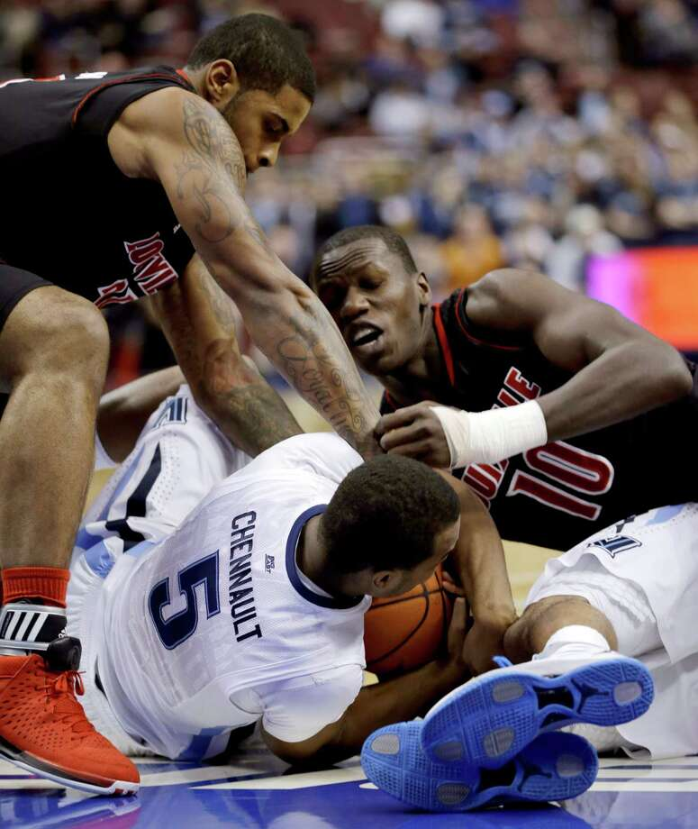 Louisville's Chane Behanan, left, and Gorgui Dieng battle for a loose ball with Villanova's Tony Chennault during the first half of an NCAA college basketball game, Tuesday, Jan. 22, 2013, in Philadelphia. (AP Photo/Matt Slocum) Photo: Matt Slocum