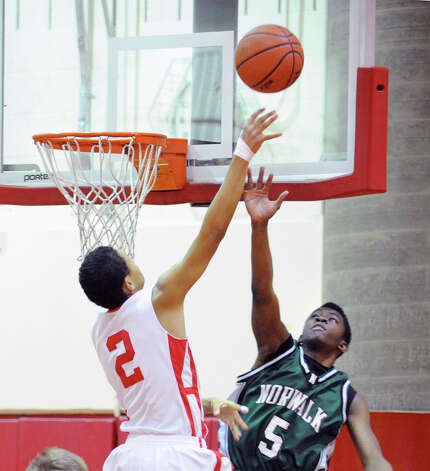 At left, CJ Byrd # 2 of Greenwich shoots the ball off the glass while being covered by Zaire Wilson # 5 of Norwalk during the boys high school basketball game between Greenwich High School and Norwalk High School at Greenwich, Tuesday night, Jan. 22, 2013. Photo: Bob Luckey / Greenwich Time