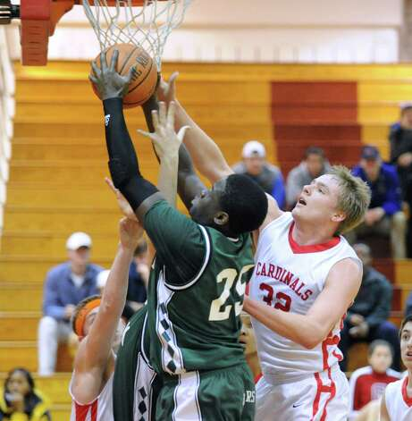 At left, Saeed Soulemane # 25 of Norwalk gets his shot blocked by Alex Wolf, right, of Greenwich, during the boys high school basketball game between Greenwich High School and Norwalk High School at Greenwich, Tuesday night, Jan. 22, 2013. Photo: Bob Luckey / Greenwich Time