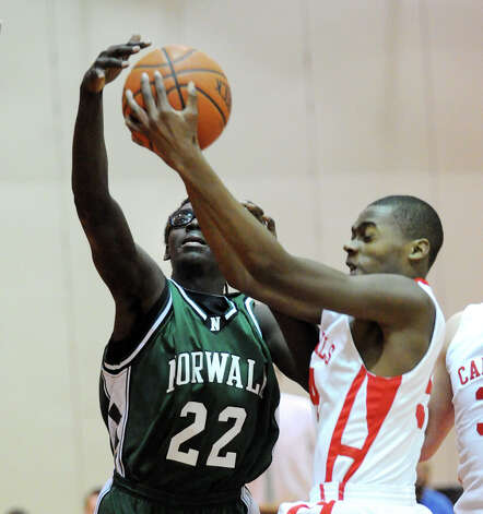At left, Roy Kane # 22 of Norwalk blocks the shot of Leonel Hyatt # 54 of Greenwich during the boys high school basketball game between Greenwich High School and Norwalk High School at Greenwich, Tuesday night, Jan. 22, 2013. Photo: Bob Luckey / Greenwich Time