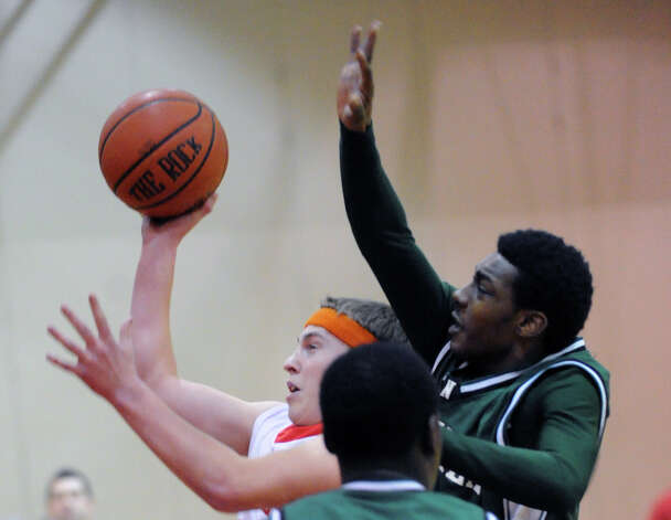 At left, Alex McMurray #11 of Greenwich throws up a runner in the lane while being covered by Jabari Dear of Norwalk during the boys high school basketball game between Greenwich High School and Norwalk High School at Greenwich, Tuesday night, Jan. 22, 2013. Photo: Bob Luckey / Greenwich Time