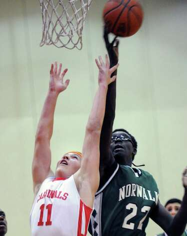 At left, Alex McMurray # 11 of Greenwich goes for a rebound against Roy Kane # 22 of Norwalk during the boys high school basketball game between Greenwich High School and Norwalk High School at Greenwich, Tuesday night, Jan. 22, 2013. Photo: Bob Luckey / Greenwich Time