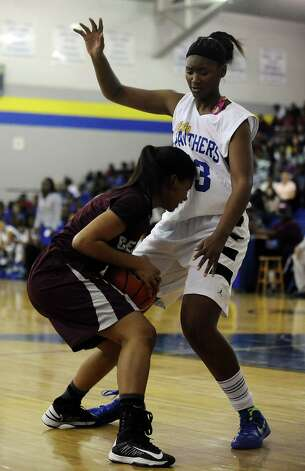 Ozen Lady Panther Jerica Bolin, #33, towers over Central Lady Jaguar Aisha Avery, #5, while looking to pass after a rebound during the Ozen High School girls basketball game against Central High School on Tuesday, January 22, 2013, at Ozen High School.  Ozen won 63 - 53. Photo taken: Randy Edwards/The Enterprise Photo: Randy Edwards