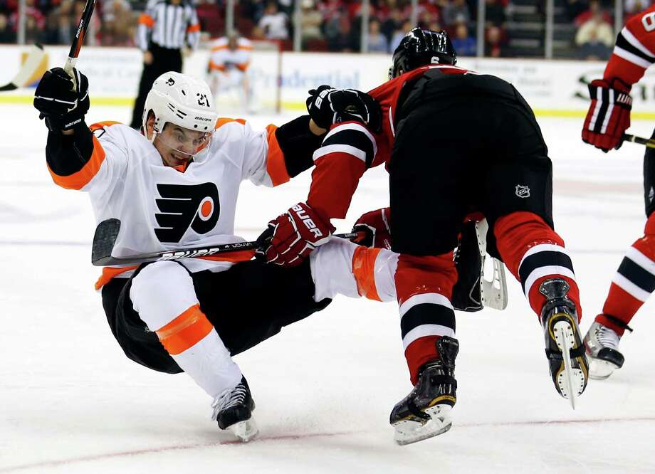 Philadelphia Flyers center Scott Laughton, left, is knocked to the ice by New Jersey Devils defenseman Andy Greene during the first period of an NHL hockey game, Tuesday, Jan. 22, 2013, in Newark, N.J. (AP Photo/Julio Cortez) Photo: Julio Cortez