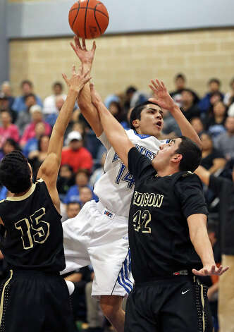 Lanier's Martin Sanchez draws a foul as he puts up a shot over Robert Muñoz (15) and Marcelo Castro of Edison. Photo: Tom Reel, San Antonio Express-News / ©2012 San Antono Express-News