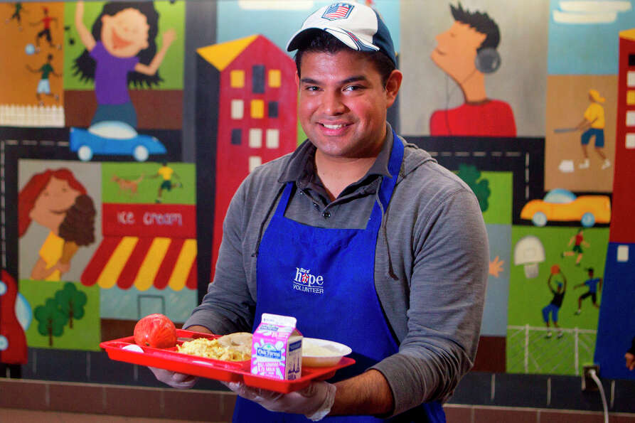 Juan Sorto holds a tray of breakfast for the homeless at the Star of Hope's Women and Family Emergen