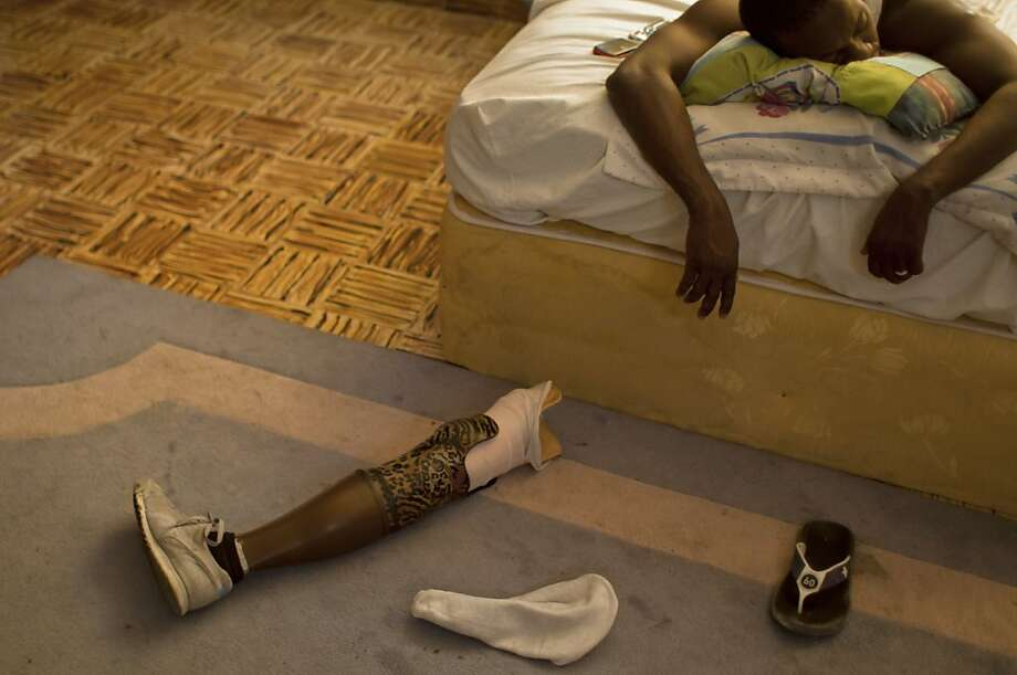 After taking off his shoes and leg,professional dancer Georges Exantus falls asleep in his bed in his Port-au-Prince home. Exantus spent three days trapped under a heap of jagged rubble after the Haitian earthquake flattened his apartment three years ago. After friends dug him out, doctors amputated his right leg just below the knee. Photo: Dieu Nalio Chery, Associated Press