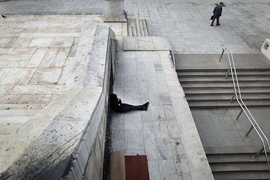 A homeless man sits near the closed entrance of a Metro station in central Syntagma square during a strike held by the unions of metro services in Athens, Tuesday, Jan. 22, 2013. Striking subway workers in Athens defied a court order to return to work and continued their protest for a sixth day on Tuesday, as demonstrations against new pay cuts escalated in the Greek capital. Photo: Petros Giannakouris, Associated Press