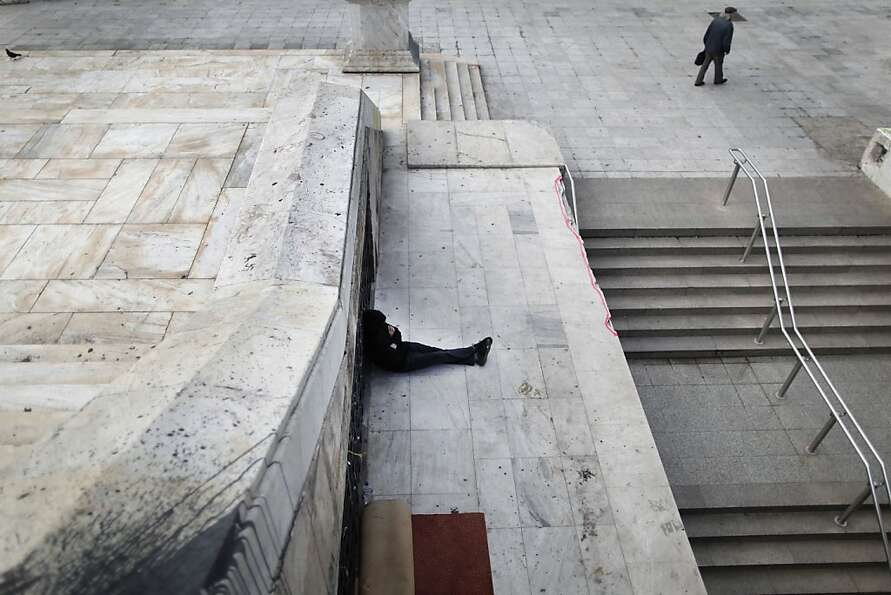 A homeless man sits near the closed entrance of a Metro station in central Syntagma square during a