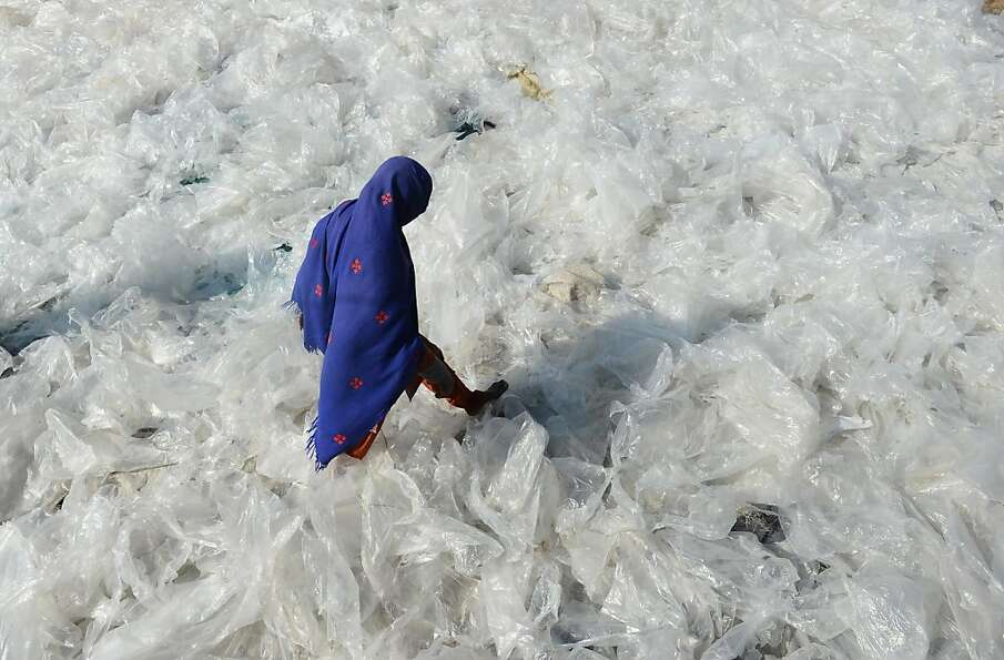 A Pakistan woman steps on recyclable plastic bags drying in the sun in Lahore on January 22, 2013.