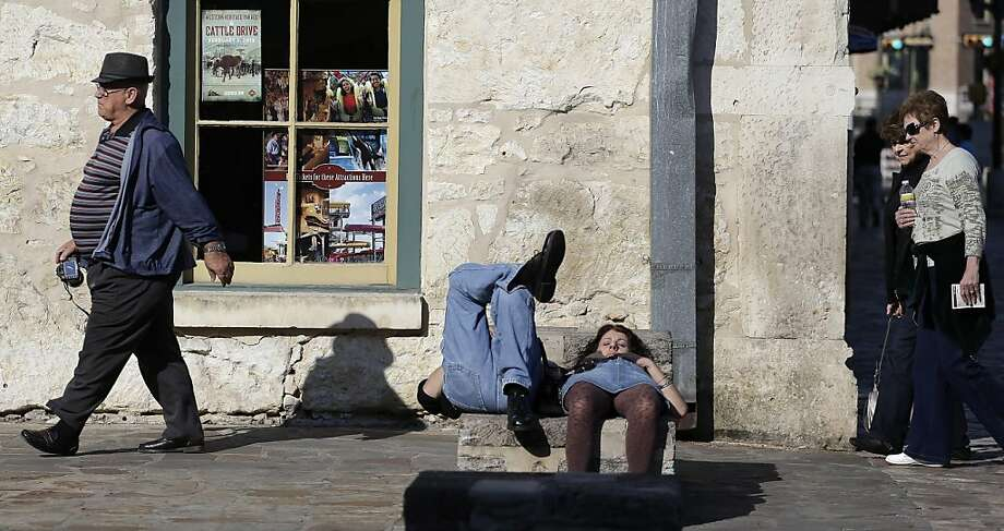 A couple nap in the sun as tourists pass by at Alamo Plaza, Tuesday, Jan. 22, 2013, in downtown San Antonio. South Texas is expecting temperatures in the low 70's this week. (AP Photo/Eric Gay) Photo: Eric Gay, Associated Press