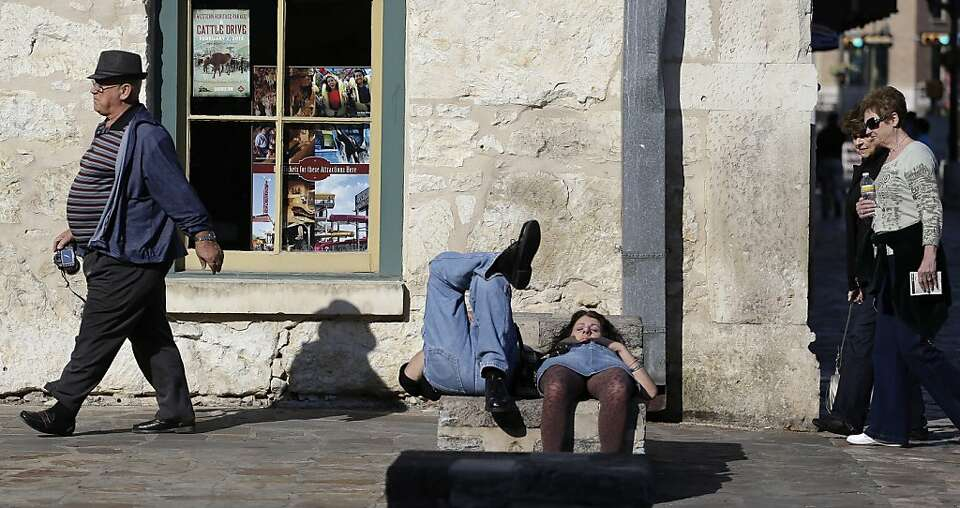 A couple nap in the sun as tourists pass by at Alamo Plaza, Tuesday, Jan. 22, 2013, in downtown San