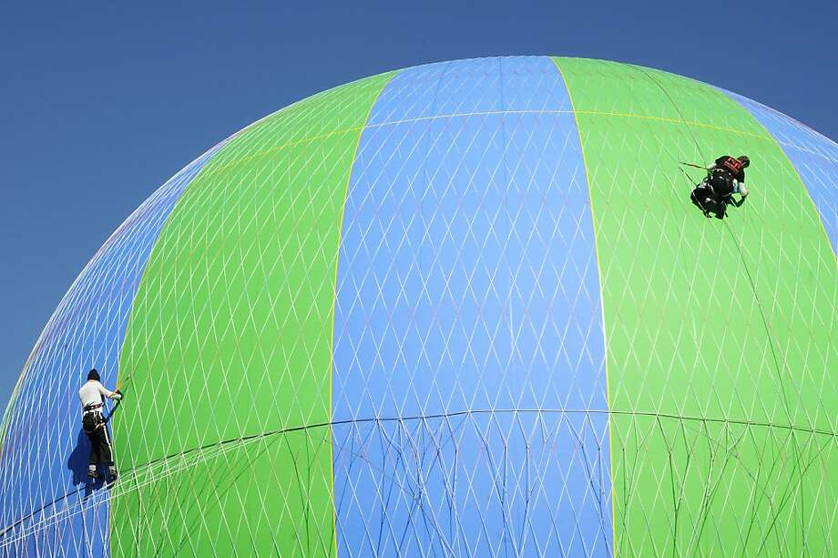 Chief Pilot Jim Klemz, left, and Pilot Bobby Rogers perform regular maintenance on a tethered helium balloon ride at Wonders of Flight attraction in Pigeon Forge, Tenn. Tuesday, Jan. 22, 2013. (AP Photo/The Mountain Press,Curt Habraken) Photo: Curt Habraken, Associated Press