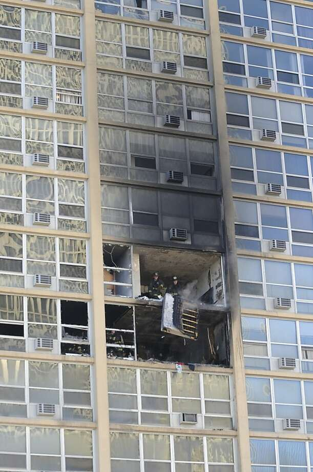 Chicago firefighters are seen inside an apartment in a high-rise building after a blaze that started on the seventh floor of the building in the city's South Shore neighborhood Tuesday, Jan. 22, 2013. The fire injured three people who were taken to area hospitals. (AP Photo/Chicago Sun-Times, Brian Jackson)  CHICAGO LOCALS OUT, MAGS OUT Photo: Brian Jackson, Associated Press