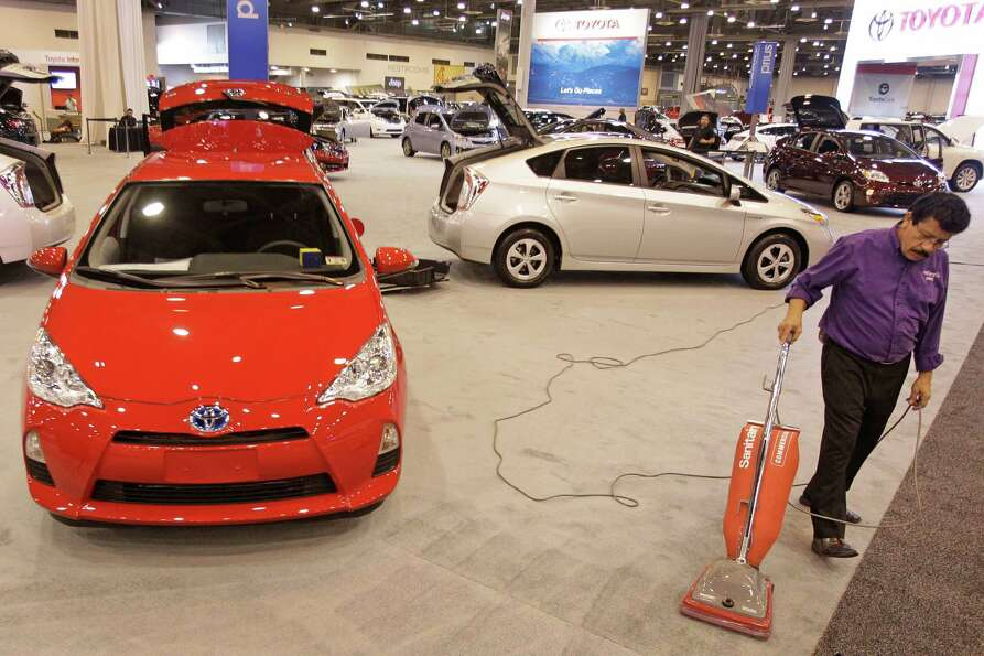 Juan Rangel vacuums around Toyota cars Tuesday, Jan. 22, 2013, in Houston as crews prepare for the o