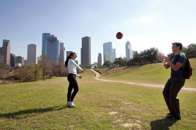 Ada Topacio, left, and Jacob Hitchen take advantage of the spring-like temperature to throw the football around at Eleanor Tinsley Park Tuesday, Jan. 22, 2013, in Houston. Photo: Brett Coomer, Houston Chronicle / © 2013 Houston Chronicle