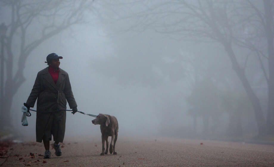 "Tina Poindexter walks her dog Argenta through the fog Wednesday, Jan. 23, 2013, in Houston. ""I think it's peaceful and mysterious,"" she said.Related story: Foggy roads are headaches for Houston commuters. Photo: Cody Duty, Houston Chronicle / © 2012 Houston Chronicle"