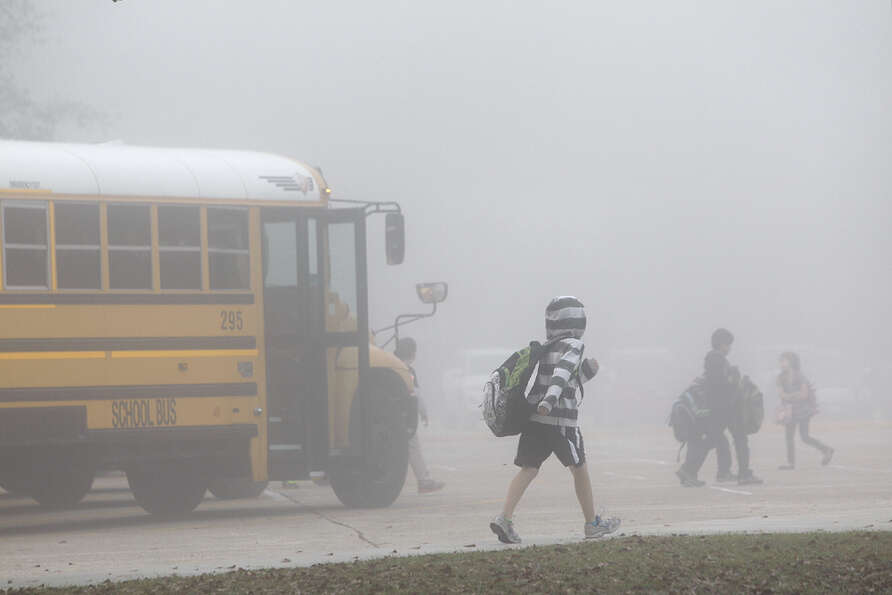 Children walk through the fog as they enter Brill Elementary,  9102 Herts Rd,  in Spring, Wednesday,