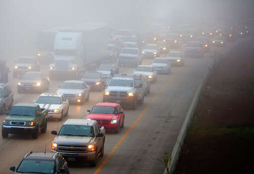 Traffic slows as fog looms on I-10 West of Houston Avenue Wednesday, Jan. 23, 2013, in Houston. Photo: Cody Duty, Houston Chronicle / © 2012 Houston Chronicle