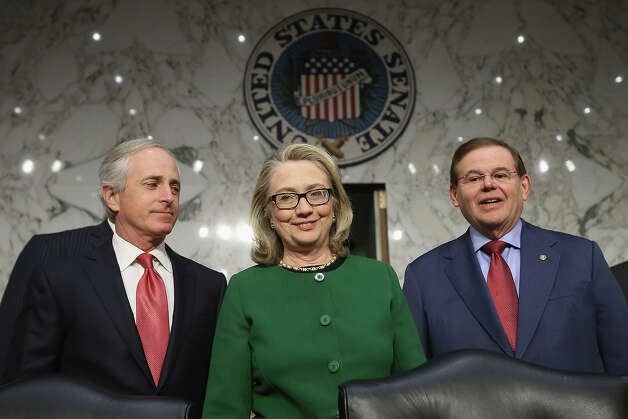 U.S. Secretary of State Hillary Clinton (C) poses for photographs with Senate Foreign Relations Committee ranking member Sen. Bob Corker (R-TN) (L) and Chairman Robert Menendez (D-NJ) before a hearing with the Senate Foreign Relations Committee on Capitol Hill January 23, 2013 in Washington, DC. Lawmakers questioned Clinton about the security failures during the September 11 attacks against the U.S. mission in Benghazi, Libya, that led to the death of four Americans, including U.S. Ambassador Christopher Stevens. Photo: Chip Somodevilla, Getty Images / 2013 Getty Images