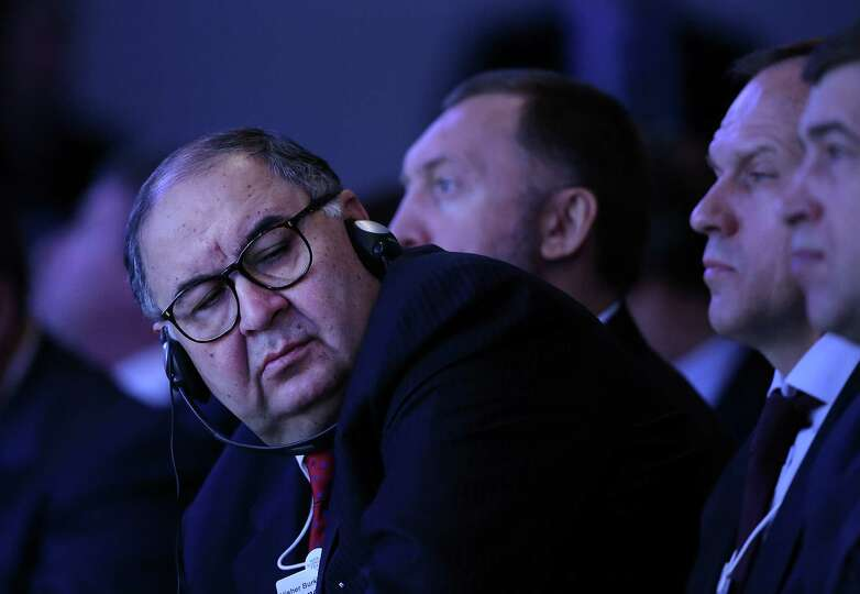 Russian billionaire Alisher Usmanov listens during the opening session on the first day of the World