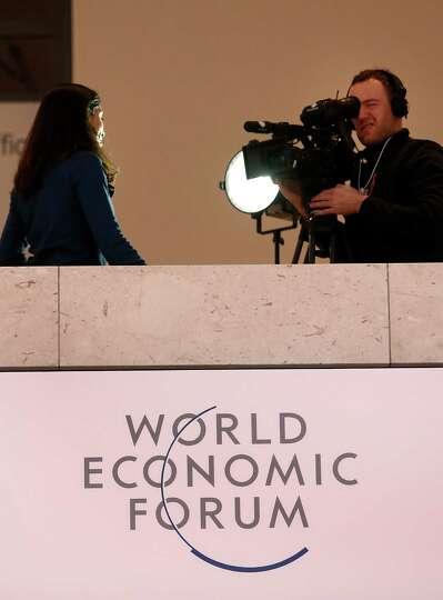 A television crew reports from inside the Congress Center on the opening day of the World Economic F