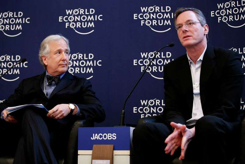Paul Jacobs, chairman and chief executive officer of Qualcomm Inc., right, speaks while Matthew Wink