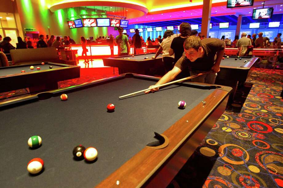 Matt Phloughouf, of The Woodlands, lines up a shot as he play pool with friends, Saturday, Jan. 12, in the Main Event in Katy.  ( Nick de la Torre / Houston Chronicle ) Photo: Nick De La Torre, Staff / © 2013  Houston Chronicle