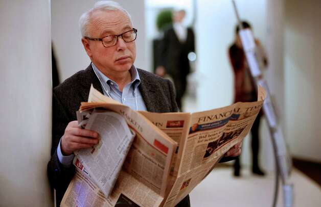 An attendee reads a newspaper in the hall during a Bloomberg Television interview on the opening day of the World Economic Forum (WEF) in Davos, Switzerland, on Wednesday, Jan. 23, 2013. World leaders, Influential executives, bankers and policy makers attend the 43rd annual meeting of the World Economic Forum in Davos, the five day event runs from Jan. 23-27. Photographer: Jason Alden/Bloomberg Photo: Jason Alden, Bloomberg / Copyright 2013 Bloomberg Finance LP, All Rights Reserved.