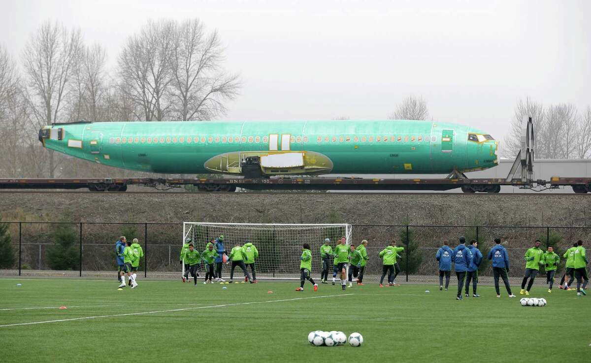 Seattle Sounders MLS soccer players line up for practice drills during training camp in Tukwila, Wash., as a Boeing 737 airplane fuselage passes by behind them on a railcar, Tuesday, Jan. 22, 2013, on the way to Boeing's assembly plant in Renton, Wash.