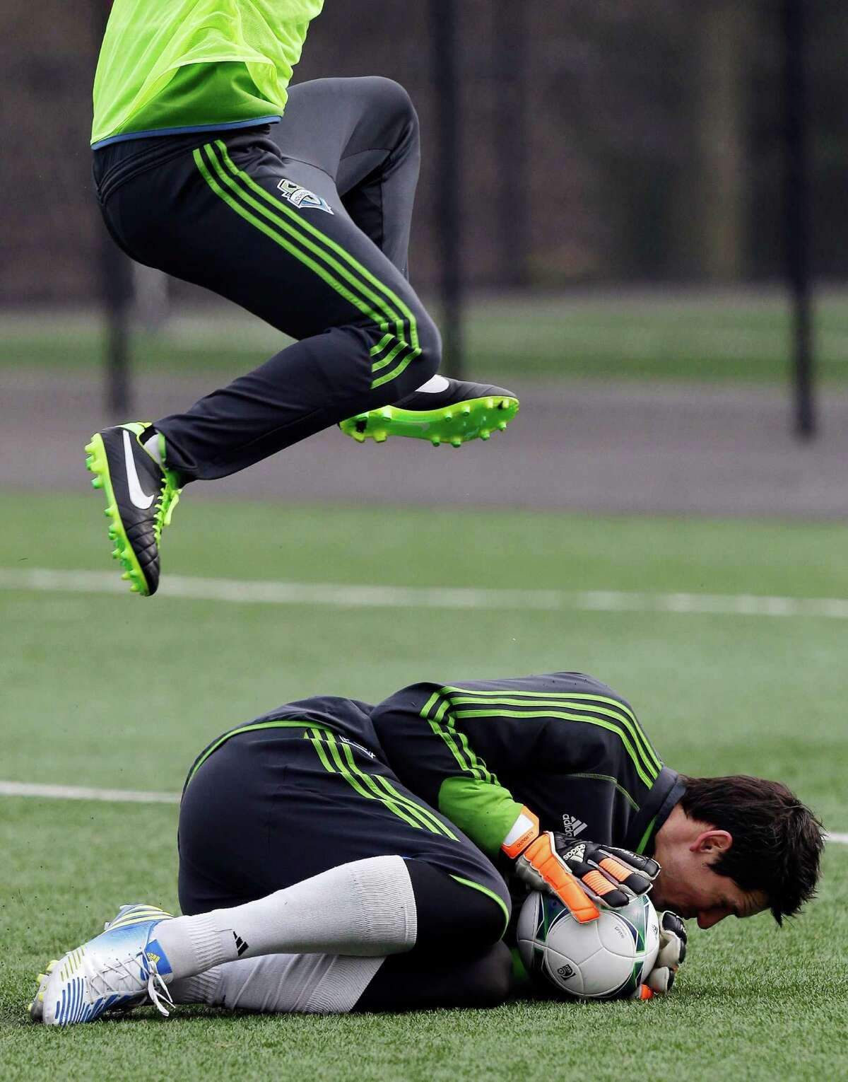 Seattle Sounders goalkeeper Michael Gspurning ducks after making a stop as a player jumps over him during MLS soccer training camp in Tukwila, Wash., Tuesday, Jan. 22, 2013.