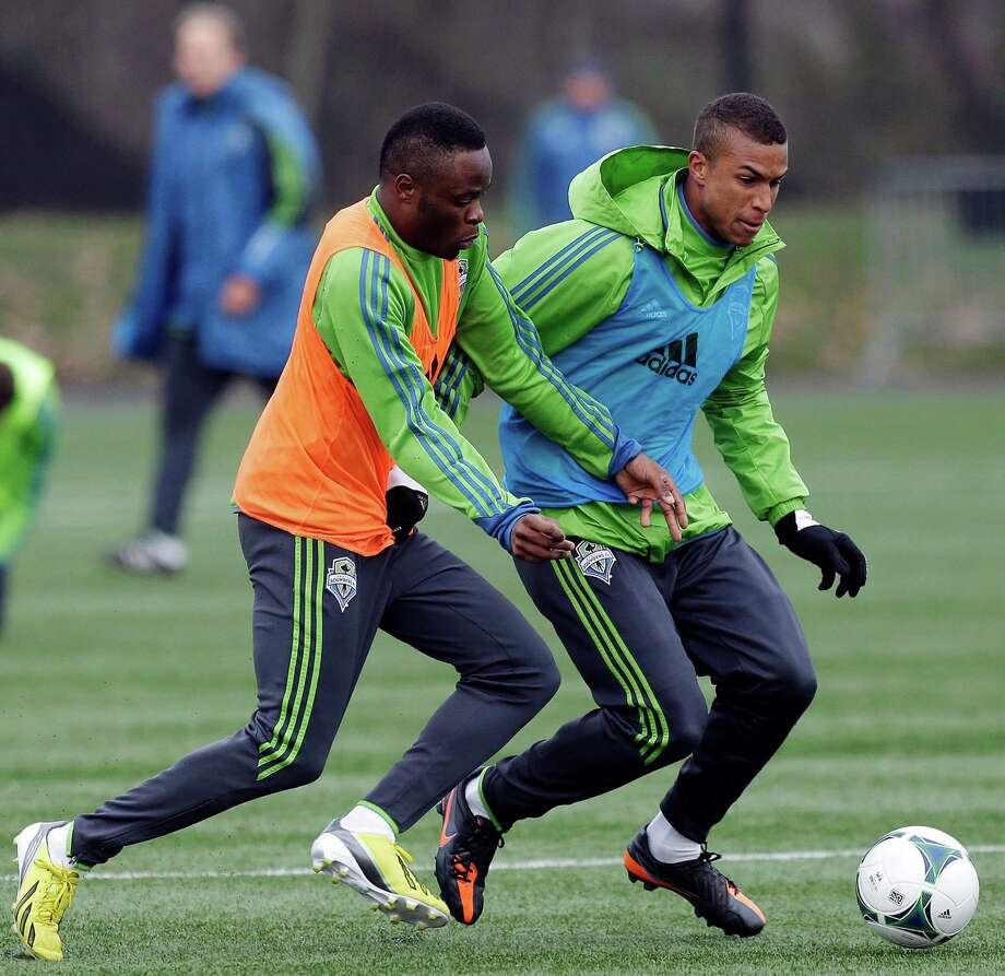 Seattle Sounders' Steve Zakuani, left, and Isaiah Schafer, right, go for the ball during an MLS soccer training camp scrimmage in Tukwila, Wash., Tuesday, Jan. 22, 2013. Photo: Ted S. Warren, Associated Press / Associated Press