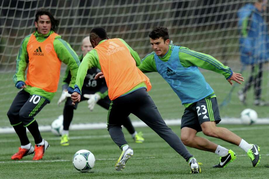 Seattle Sounders' Steve Zakuani, center, drives around Servando Carrasco (23) as Mauro Rosales (10) watches during an MLS soccer training camp scrimmage in Tukwila, Wash., Tuesday, Jan. 22, 2013.  Photo: Ted S. Warren, Associated Press / Associated Press