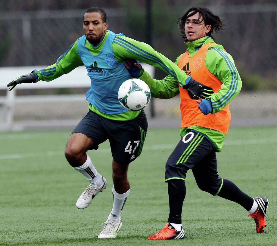 Seattle Sounders' Mauro Rosales, right, and Ross LaBauex, left, battle for the ball during an MLS soccer training camp scrimmage in Tukwila, Wash., Tuesday, Jan. 22, 2013.  Photo: Ted S. Warren, Associated Press / Associated Press