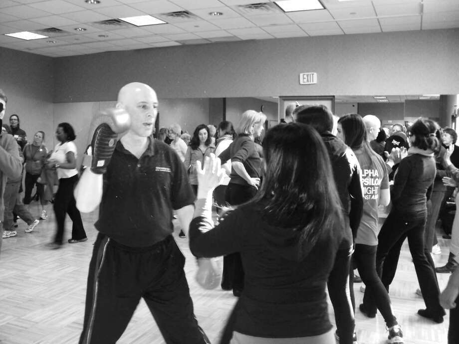 Instructor Frank Drake coaches participants on various methods of defense against an attack at The Junior League of Greenwich and the YWCA Greenwich's second annual Women's Self Defense Class, which was held recently at the Y. Photo: Contributed Photo